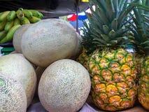Cantaloupmelon och ananors på en ställning royaltyfria bilder