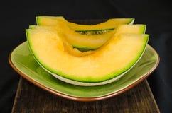 Cantaloupmelonskivor på en platta Arkivfoto
