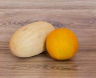 Cantalupo acerbo due ancora che cresce sulle loro viti Immagini Stock