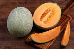 Cantalupo orgânico com os utensílios na tabela de madeira Fotos de Stock