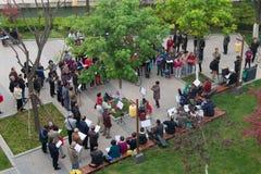 Cantando y jugando música en parque al lado de ciudad emparede Xian Imagen de archivo libre de regalías