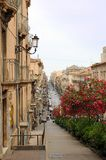 Catania street scene. Long street with colorful trees and buildings, Catania city, Sicily, Italy stock photography