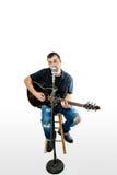 Cantante Acoustic Guitarist sull'espressione sollevata bianco immagine stock