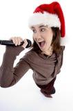 Cantante adolescente con el mic y el sombrero de la Navidad Foto de archivo libre de regalías