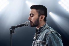 Cantante asiático que canta con el micrófono imagenes de archivo