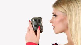 Cantante canta in un retro microfono Priorità bassa bianca Vista laterale Fine in su archivi video