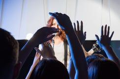 Cantante con la guitarra sobre las manos felices de las fans Foto de archivo libre de regalías