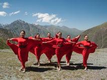 Cantante con los bailarines en montañas en Kirguistán imagenes de archivo