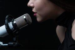 Cantante davanti ad un microfono Isolato su un fondo scuro immagine stock