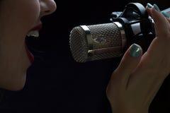 Cantante davanti ad un microfono Isolato su un fondo scuro fotografie stock libere da diritti
