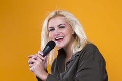 Cantante de la muchacha con el micrófono foto de archivo