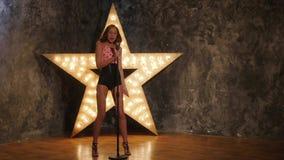 Cantante de la mujer con el micrófono, estrella brillante en almacen de metraje de vídeo