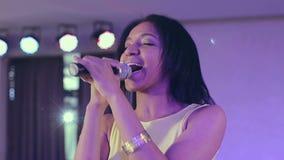 Cantante de piel morena del jazz de la mujer negra que canta una canción en etapa en el micrófono metrajes
