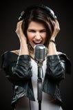 Cantante de roca con el micrófono y los auriculares Imagen de archivo