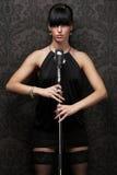 Cantante de sexo femenino atractivo que desgasta la alineada negra que lleva a cabo un r Fotos de archivo