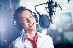 Cantante de sexo masculino asiático produciendo la canción en el estudio de grabación Imagen de archivo