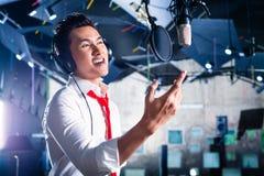 Cantante de sexo masculino asiático produciendo la canción en el estudio de grabación Fotografía de archivo libre de regalías