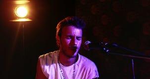 Cantante de sexo masculino que canta en un micrófono 4k metrajes