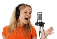 Cantante en auriculares que canta con el micrófono imagen de archivo