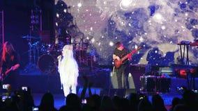 Cantante en escena, cantante de roca que se realiza en el concierto vivo, banda de rock, vocalista delante de la pantalla llevada