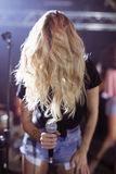 Cantante femminile che copre il suo fronte di capelli mentre eseguendo al night-club Fotografia Stock Libera da Diritti