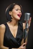 Cantante femminile con gli occhi chiusi che tengono microfono Fotografia Stock