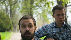 Cantante, guitarrista y batería pasando con almacen de video