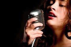 Cantante hermoso que canta con el micrófono imagen de archivo