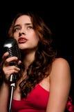 Cantante hermoso que canta con el micrófono Imagen de archivo libre de regalías