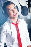 Cantante maschio asiatico producendo canzone in studio di registrazione Immagine Stock