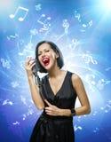 Cantante que guarda el micrófono contra fondo azul de la música con las notas Foto de archivo libre de regalías