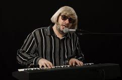 Cantante que se acompaña en piano eléctrico Imagen de archivo libre de regalías