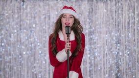 Cantante in un costume nubile della neve canta le canzoni in un retro microfono Priorità bassa di Bokeh video d archivio