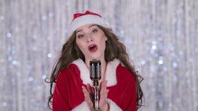Cantante in un costume nubile della neve canta le canzoni in un retro microfono Priorità bassa di Bokeh Fine in su stock footage