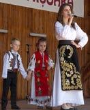 Cantante y niños rumanos, en traje tradicional Imagenes de archivo