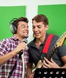 Cantantes con el micrófono y la guitarra que se realizan en la registración de Studi foto de archivo