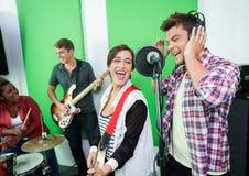 Cantantes emocionados que se realizan mientras que colegas que juegan Inst musical foto de archivo