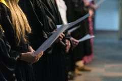 Cante a coro a los cantantes que llevan a cabo la partitura musical y que cantan en gradu del estudiante imágenes de archivo libres de regalías