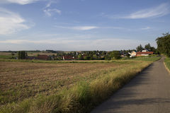 Canted field near the road and the village in the background Stock Image