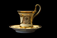 Canteen cup on a saucer. Beautiful dining room with a cup on a saucer with gold Royalty Free Stock Photos