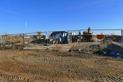 Canteiro de obras com as máquinas escavadoras para as casas de construção cercadas Fotos de Stock