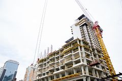 Canteiro de obras Os guindastes de torre industriais grandes com elevação inacabado aumentaram construções e o céu azul no fundo  fotografia de stock