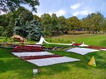 Canteiros de flores decorativos sob a forma das toalhas bordadas com as meninas ucranianas nas grinaldas e nos fundos da grama ve Imagens de Stock Royalty Free