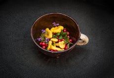 Cantharellen, vossebessen lingonberries, thyme in de klei pipkin schotel op zwarte achtergrond Stock Fotografie