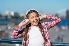 Canti la felicità Cuffie felici di usura del bambino Poco fan della musica Bambina felice La bambina ascolta musica all'aperto immagini stock