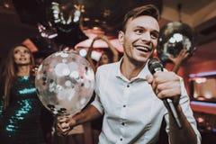 Canti nel karaoke Gli uomini si divertono il grande umore aerostato immagini stock
