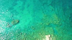 Cantidad aérea de la oleada de ondas en una costa rocosa con agua azul clara almacen de metraje de vídeo