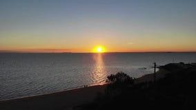 Cantidad aérea de la puesta del sol sobre la playa con caminar de la gente almacen de video