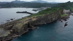 Cantidad aérea de los acantilados cerca del océano con las porciones de gente que camina en el top almacen de metraje de vídeo