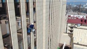 Cantidad aérea de un alpinista industrial en el lado de un edificio almacen de video
